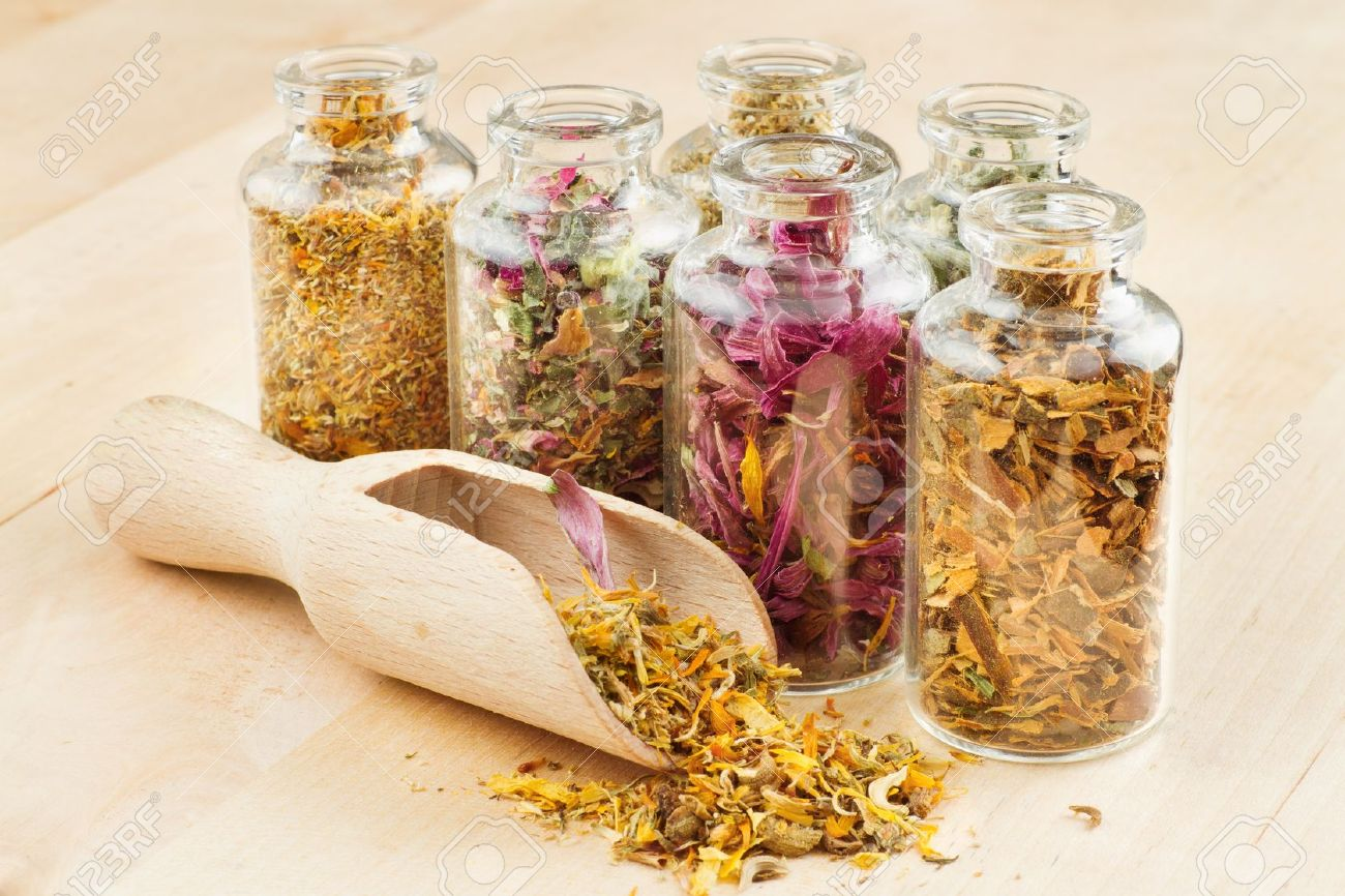 16577752-healing-herbs-in-glass-bottles-and-wooden-scoop-herbal-medicine-Stock-Photo